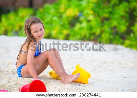 Adorable little girl playing with beach toys during tropical vacation - stock photo