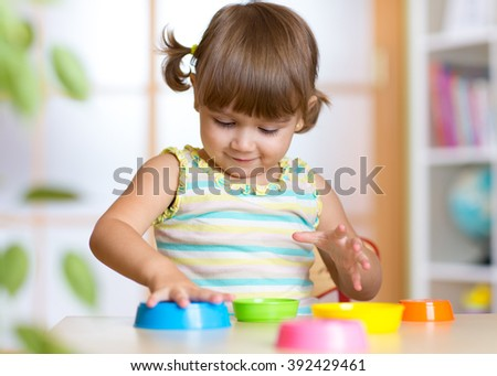 Adorable little girl playing with cup toys, smiling.