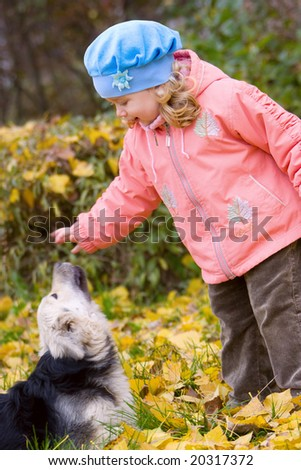Adorable little girl playing with dog in autumn park - stock photo