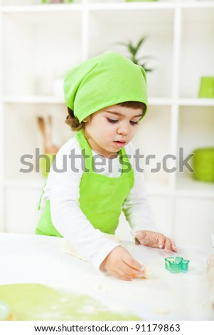 Adorable little girl playing with dough in the kitchen