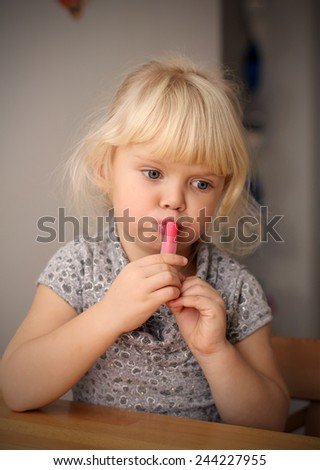 Adorable little girl playing with mommy's make up. portrait of the little girl with lipstick  - stock photo