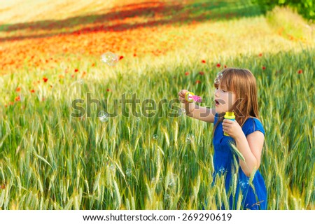 Adorable little girl playing with soap bubbles on a nice summer day - stock photo