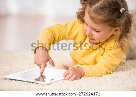 Adorable little girl playing with tablet, lying on the floor. - stock photo