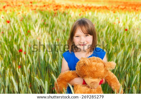 Adorable little girl playing with teddy bear in wheat field on a very hot summer day, wearing blue dress - stock photo