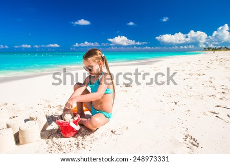 Adorable little girl playing with toys during beach vacation