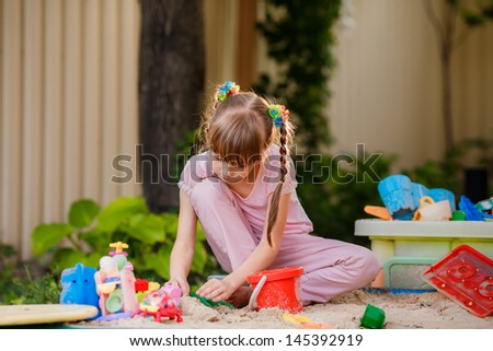 Adorable little girl playing with toys in a sandbox
