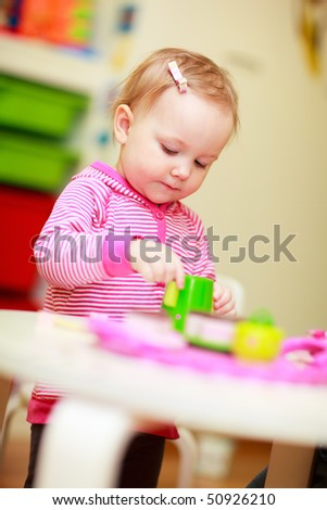 Adorable little girl playing with toys in her room - stock photo