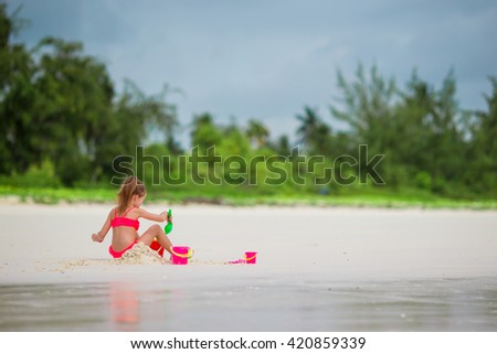 Adorable little girl playing with toys on the beach - stock photo