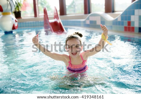 Adorable little girl  playing with water splashes at indoor  pool  - stock photo