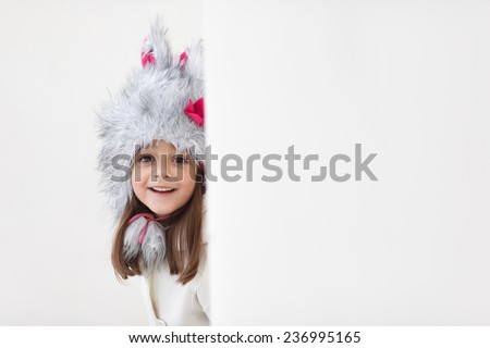 Adorable little girl posing and smiling in to a camera. Wearing winter coat and hat. Lovely young girl in the winter outdoors. Copy space. Lovely child trying to scare behind white wall. - stock photo