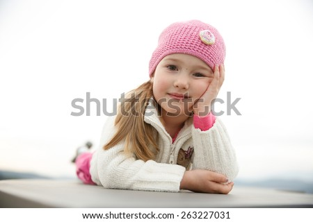 Adorable little girl posing for a picture, laid down on a wall, smiling - stock photo