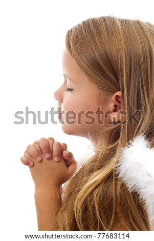 Adorable little girl praying peacefully - isolated, closeup - stock photo