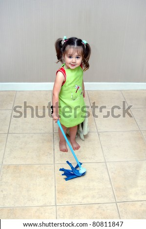 Adorable little girl pushes her mop back and forth cleaning the floors.  She is learning household chores from her mom.  She is wearing a green apron and holding a blue, play, mop. - stock photo