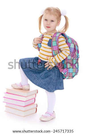 Adorable little girl put her foot on a stack of books.Isolated on white background - stock photo