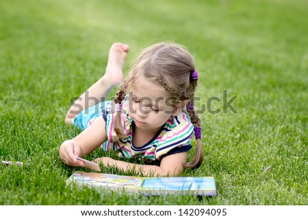 Adorable little girl reading book in the garden - outdoor - stock photo
