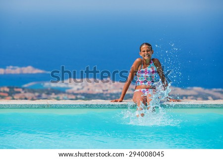 Adorable little girl relaxing at swimming pool - stock photo