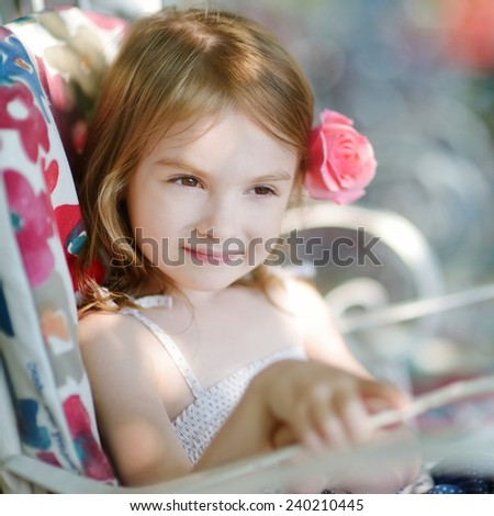 Adorable little girl relaxing in outdoor restaurant - stock photo