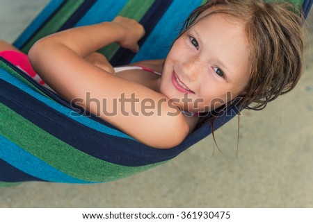 Adorable little girl resting in a hammock on the beach - stock photo