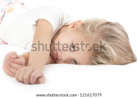 Adorable little girl resting in bed and looking at the camera close-up on white - stock photo