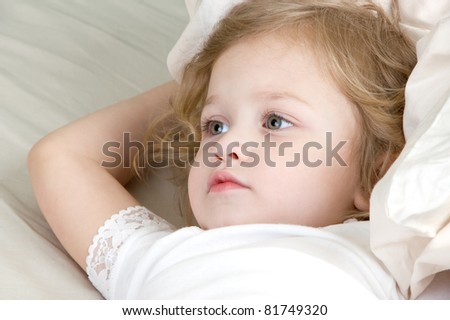 Adorable little girl resting in the bed close-up