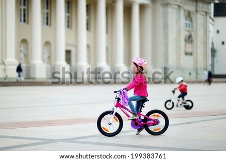 Adorable little girl riding a bike in a city - stock photo