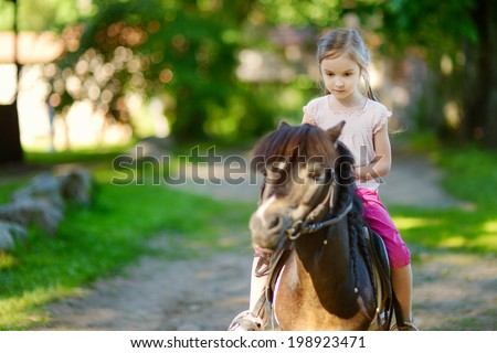 Adorable little girl riding a pony at summer - stock photo
