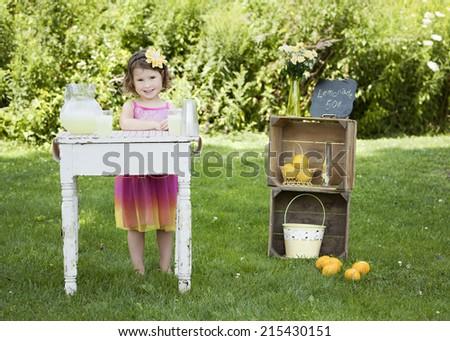 Adorable little girl running a lemonade stand. - stock photo