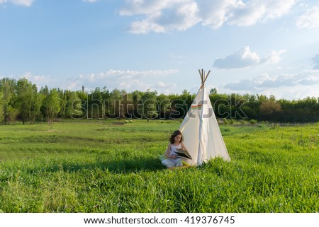 Adorable little girl sitting in a tent teepee - stock photo