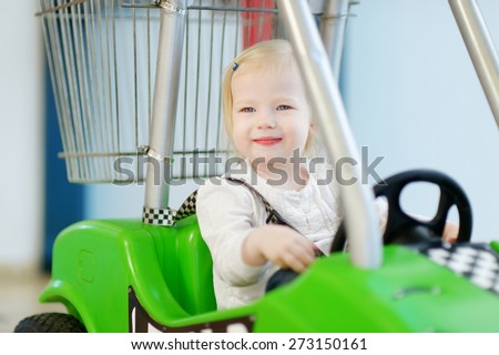 Adorable little girl sitting in shopping cart - stock photo