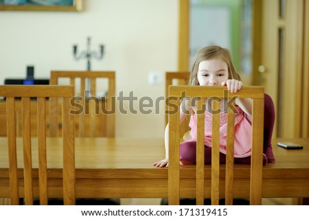 Adorable little girl sitting on a table at home - stock photo