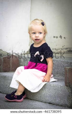 Adorable little girl sitting on stairs on warm and sunny day