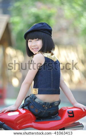 Adorable little girl sitting on the red toy motorbike.
