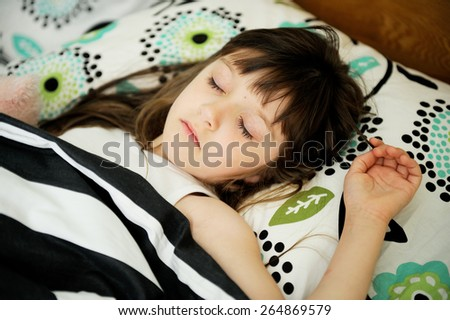 Adorable little girl sleep in the bed on sunny morning - stock photo