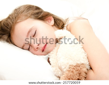 Adorable little girl sleeping with toy in her bed