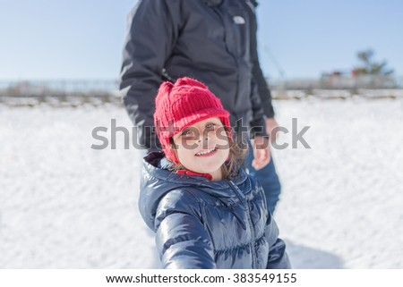 Adorable little girl smiling at camera while standing outdoors in winter time. - stock photo