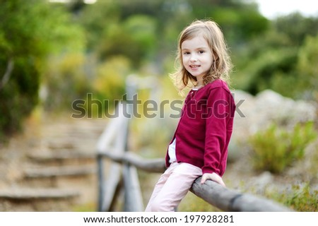 Adorable little girl smiling outdoors - stock photo