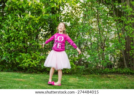 Adorable little girl spinning around in a beautiful park on a nice day, wearing tutu skirt, ballerina shoes and bright pink t-shirt - stock photo