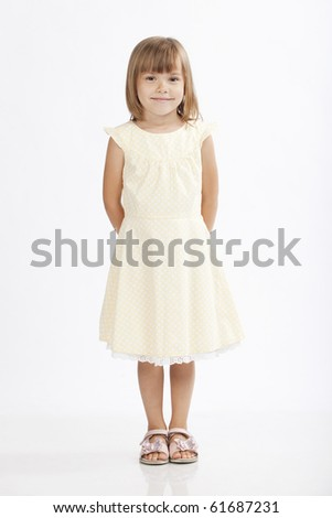 Adorable little girl standing and hiding her hands - stock photo