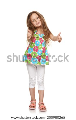 Adorable little girl standing in full length and showing double thumbs up, over white background - stock photo