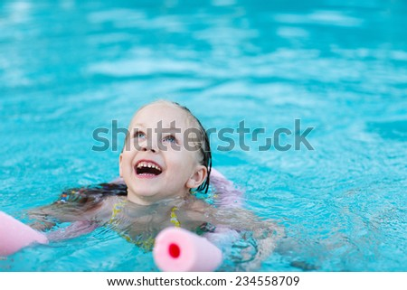 Adorable little girl swimming with a pink foam noodle in a pool while on summer vacation - stock photo