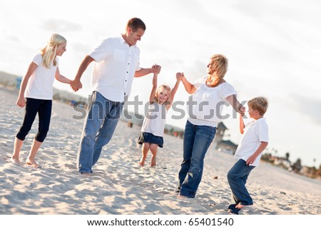 Adorable Little Girl Swinging with Her Parents and Family at the Beach. - stock photo