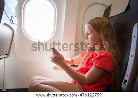 Adorable little girl traveling by an airplane.