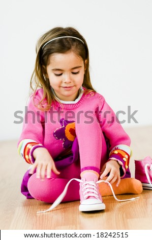adorable little girl tying her shoes - stock photo