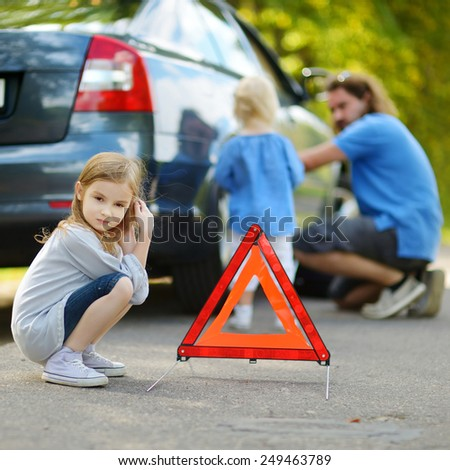 Adorable little girl waiting by the red warning triangle sign while her father is changing a car wheel outdoors on beautiful summer day - stock photo