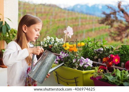 Adorable little girl watering flowers on the balcony - stock photo