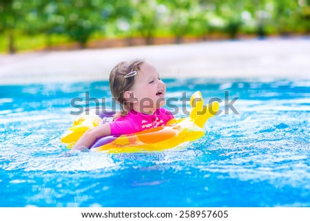 Adorable little girl wearing a colorful sun protection swimming suit playing with water splashes at beautiful pool in a tropical resort having fun during family summer vacation - stock photo