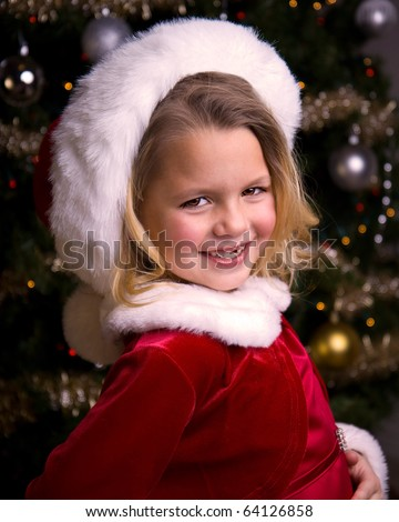Adorable little girl wearing a Santa Hat and Dress in front of a Christmas tree