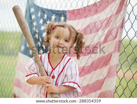 Adorable little girl wearing a vintage baseball uniform, holding a baseball bat and standing in front of an American Flag hanging from a chain link fence.   - stock photo