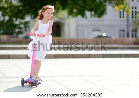 Adorable little girl wearing beautiful dress riding her scooter in a summer park - stock photo