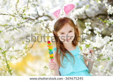 Adorable little girl wearing bunny ears eating colorful gum candies on a stick in blooming cherry garden on Easter day - stock photo